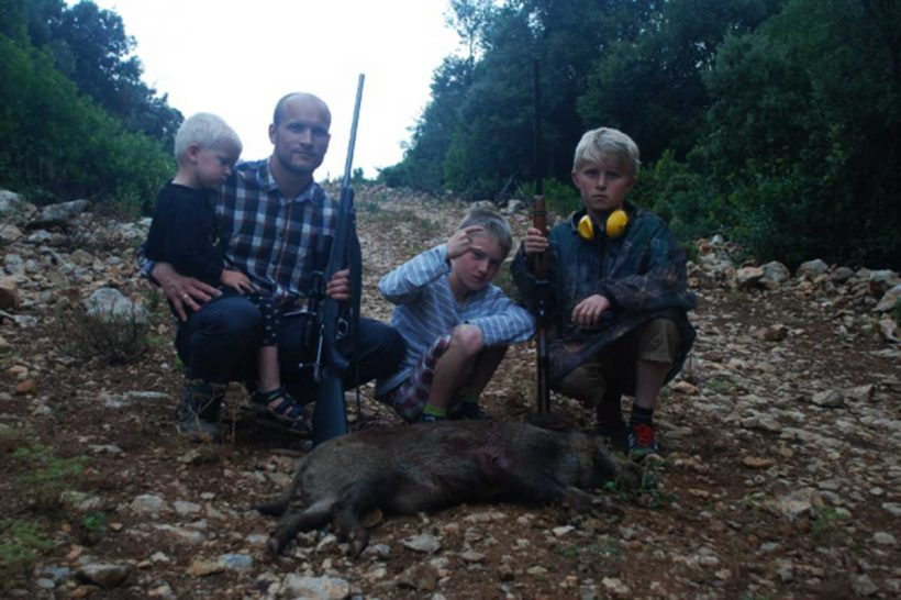 Father and three sons with wild boar on pose